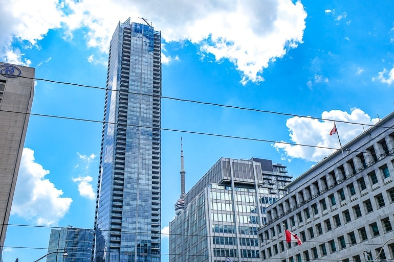 tall glass skyscraper with hotel buildings around in downtown toronto