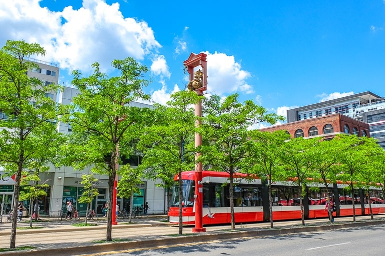 long red street car with green trees in front in toronto chinatown