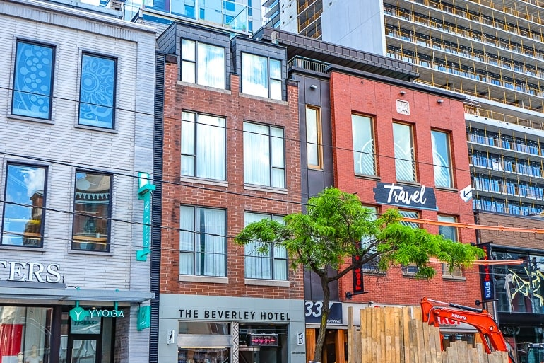 small hotel among brick buildings with shop fronts in toronto on queen street