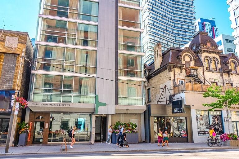slim glass templar hotel building with people walking on sidewalk