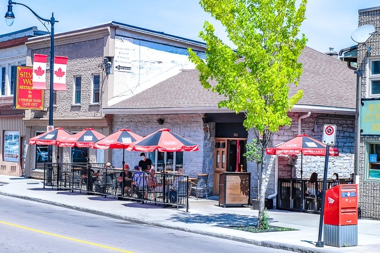 small bar in stone house with sidewalk patio and umbrellas in kingston ontario