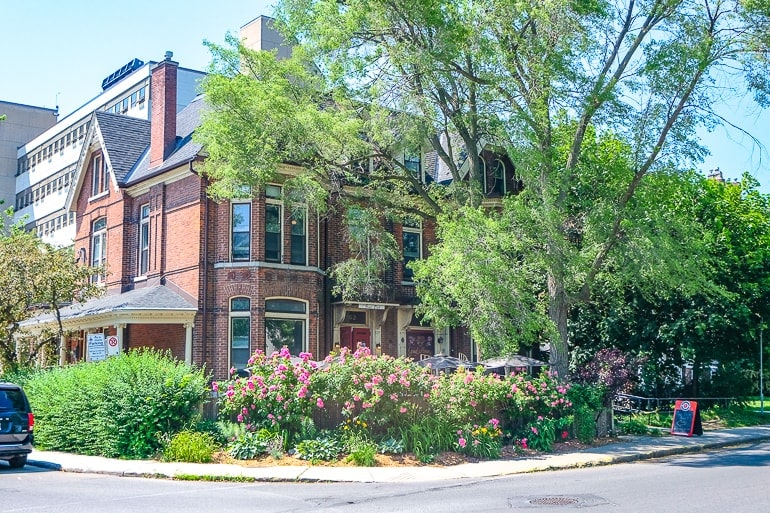 red brick house with pub hidden by trees in kingston ontario