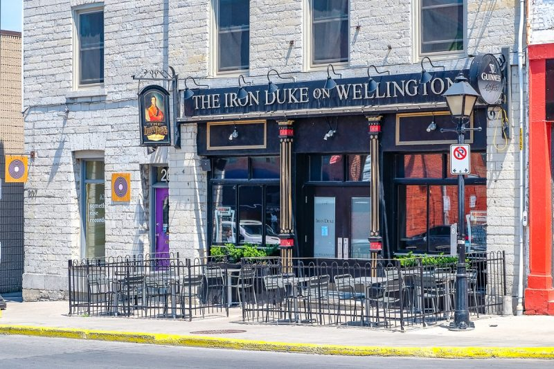 exterior of pub with patio chairs on sidewalk in kingston ontario