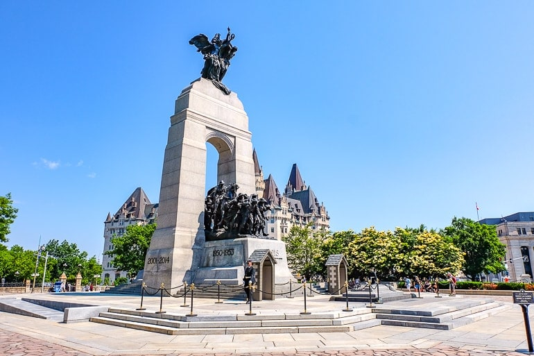 large stone arch monument with statues under in ottawa
