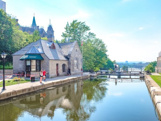 girl standing at edge of water in rideau canal lock one day in ottawa