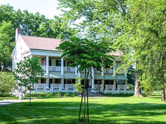 old white house with veranda through green trees ontarios finest inns