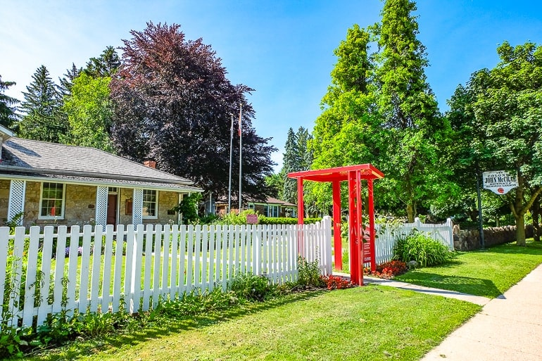 old house behind white fence with red gate and trees mccrae house things to do in guelph