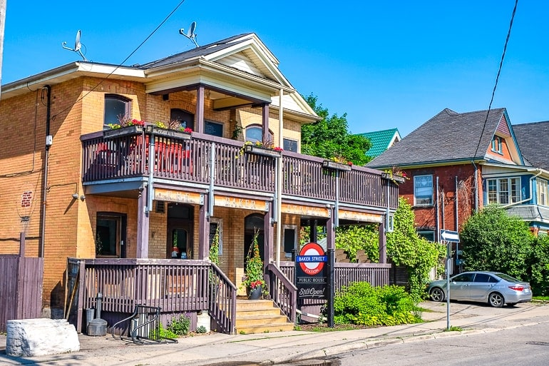 old yellow house with front patios and pub sign baker street pub guelph