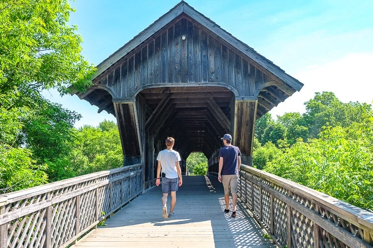 two guys crossing wooden covered bridge in guelph ontario