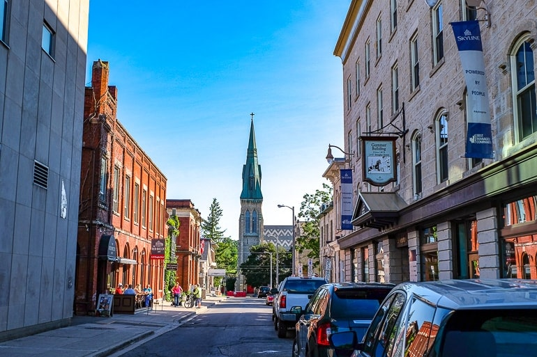 city street with buildings and church at the end guelph ontario downtown