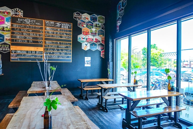 wooden tables inside shop with beer menu on wall royal city brewery guelph
