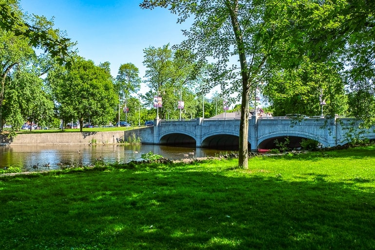 bridge with river under and green park in front royal city park guelph ontario