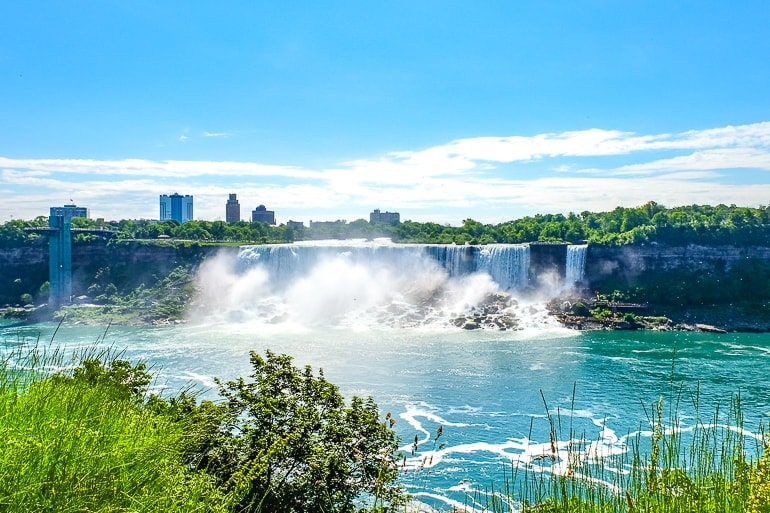 waterfalls from a distance with green shrubs in front american falls niagara falls