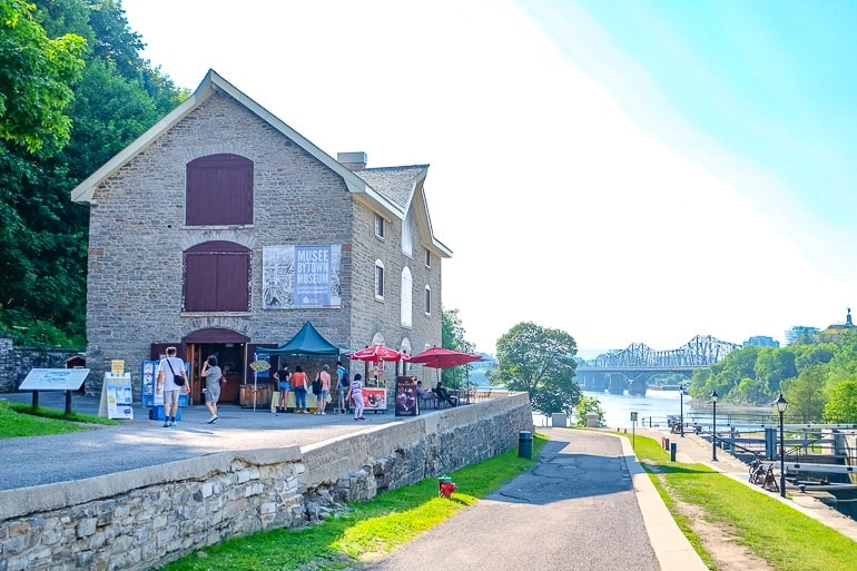 old stone house turned museum beside locks with Ottawa river in background