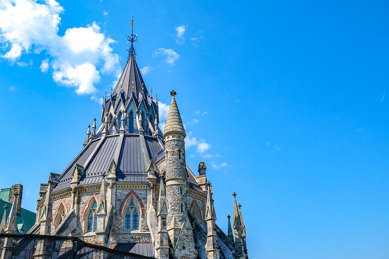 round library of parliament with metal spire and blue sky things to do in ottawa canada