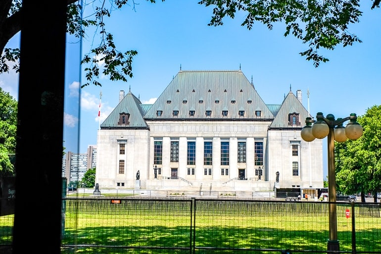 white and grey court building with green lawn in front supreme court of canada in ottawa