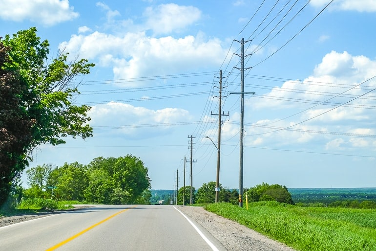 rural paved road with green field and hydro poles toronto to barrie driving