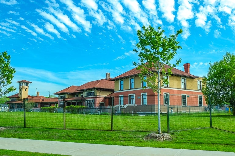 yellow and red train station with green grass and fence in front barrie go station allandale