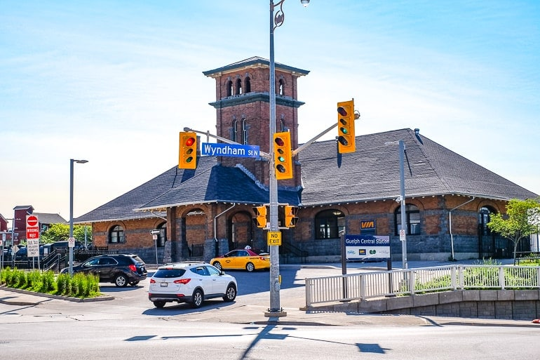 red train station with tower and cars parked in front toronto to guelph central station