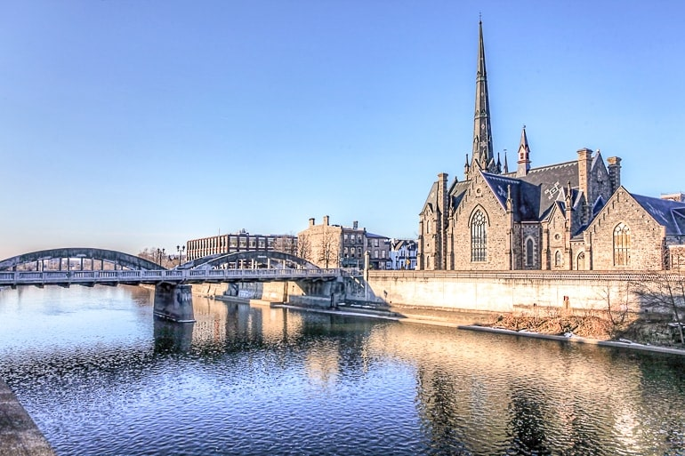 stone church with spire along blue river with bridge cambridge ontario day trip toronto