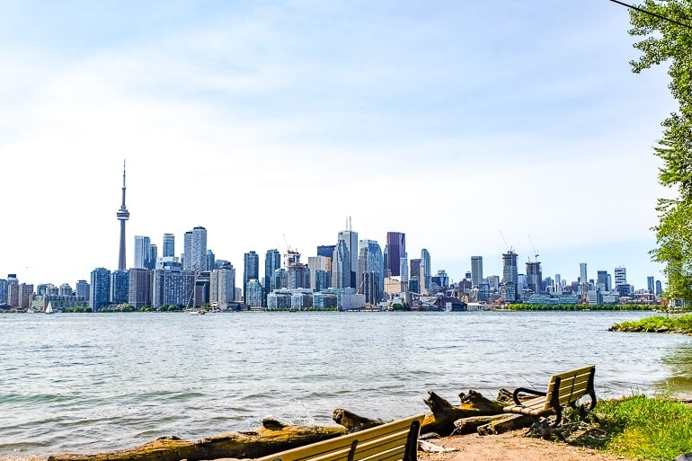 toronto buildings skyline with lake and benche in foreground toronto islands day trip