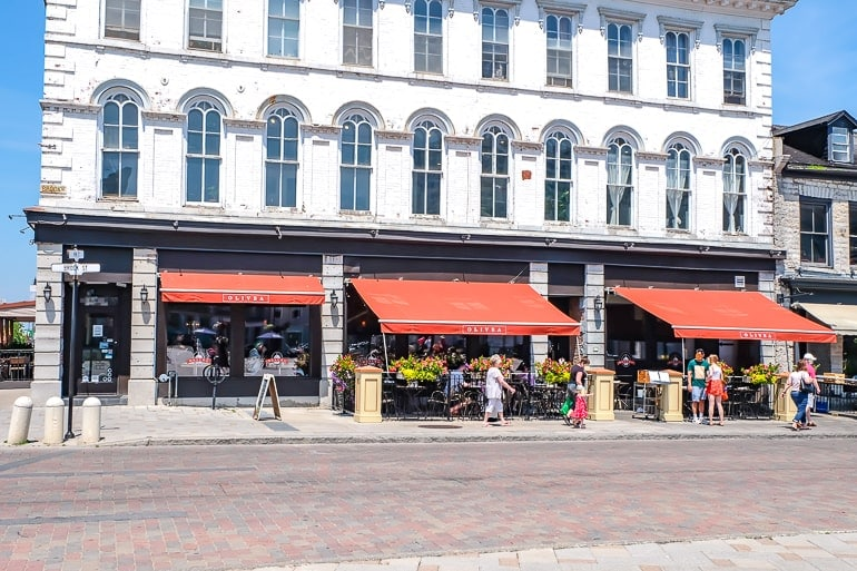 italian restaurant with orange patio covers and sidewalk beside
