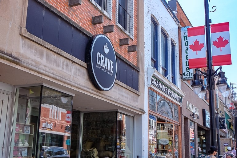 coffee shop sign against red brick building with canada flags behind crave kingston