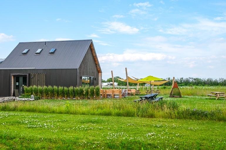 grey barn building with green fields around prince edward county winery
