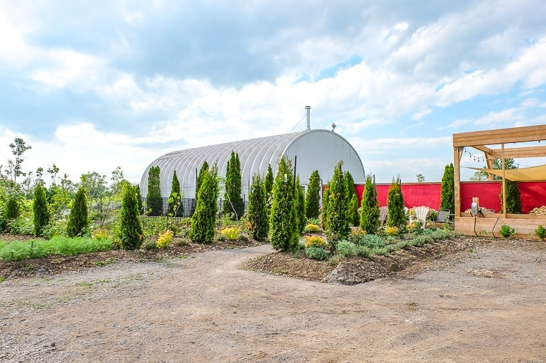 metal barn dome with green trees in front of winery