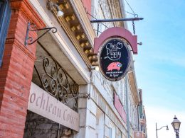 hanging restaurant sign over sidewalk with red brick wall beside restaurants in kingston ontario