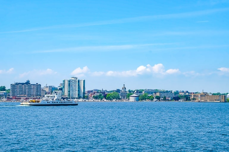 ferry boat crossing lake with city behind kingston ontario waterfront