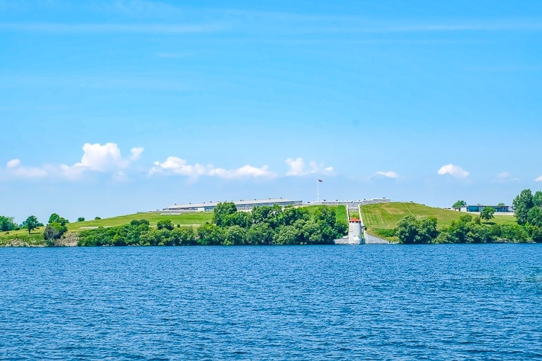 blue lake with green hill and old fort henry behind kingston ontario