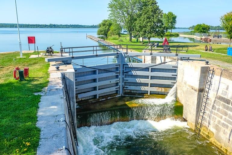 waterway lock gates with blue lake and green park behind kingston mills locks