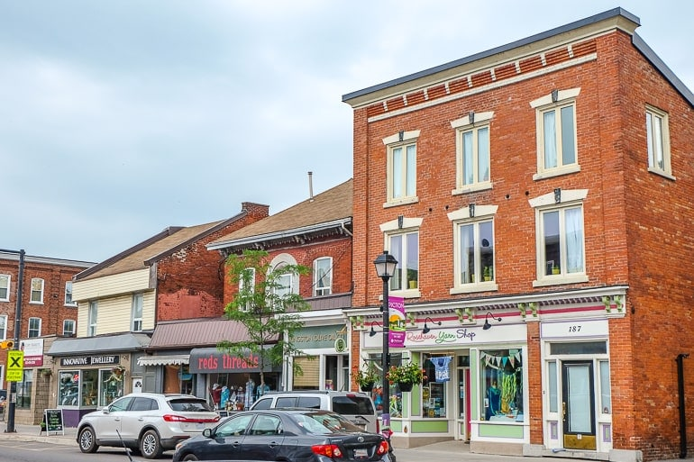 red brick buildings with storefronts and cars parked picton ontario