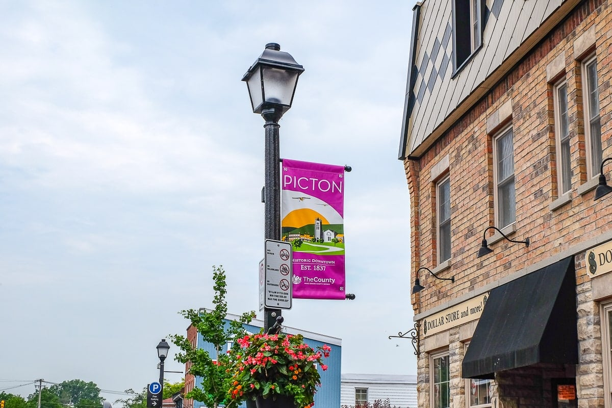 pink town sign on lamp pole where to stay in prince edward county accommodations