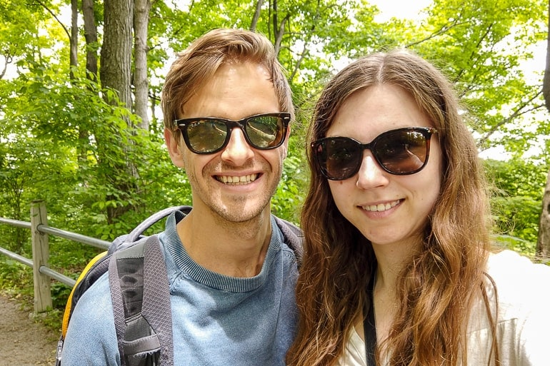 man and woman with sunglasses posing for a photo in the forest ontario away