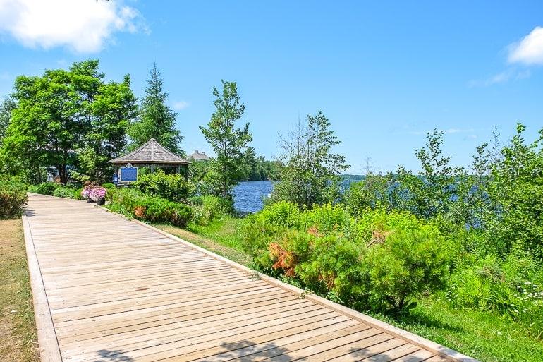 wooden boardwalk by lake with flowers and blue sky muskoka wharf gravenhurst