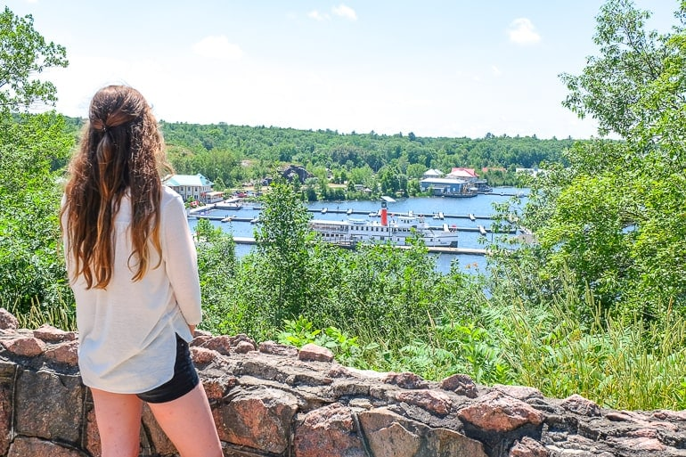 woman standing at rocky lookout overlooking ship in lake gravenhurst ontario