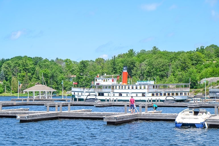 old white steam ship parked at wooden dock in blue lake things to do in gravenhurst ontario