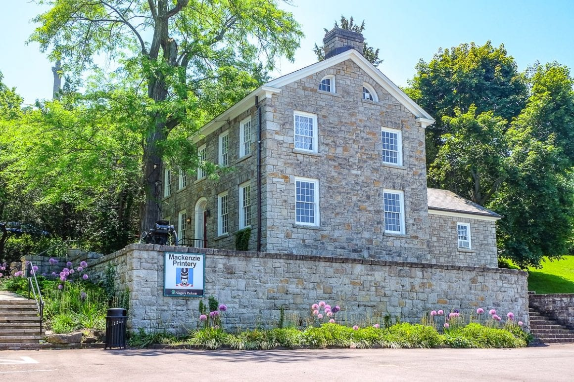 grey limestone building with trees behind museum in niagara on the lake