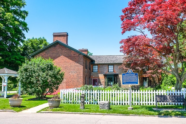 red brick house with white fence in front and trees around things to do in niagara on the lake