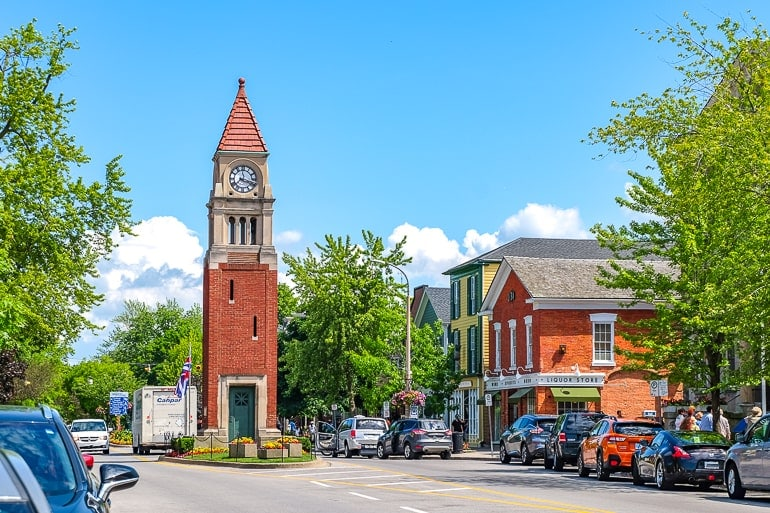 brick clock tower on middle of street with cars parked