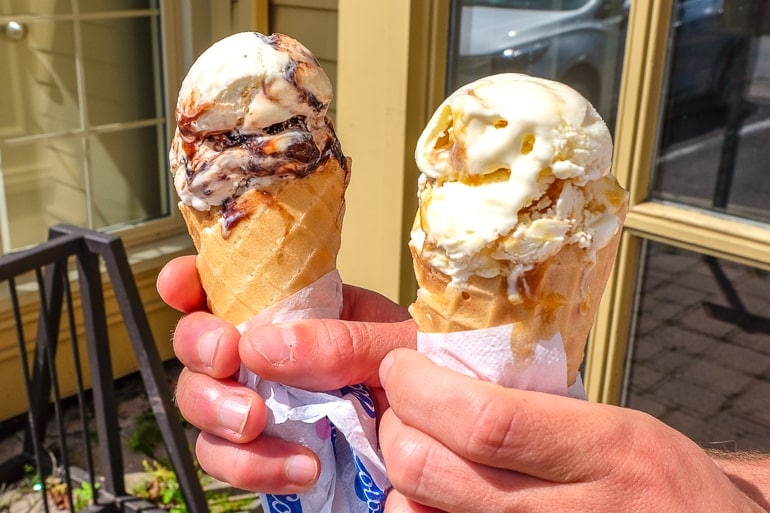 two ice cream cones in hand from cows in niagara on the lake