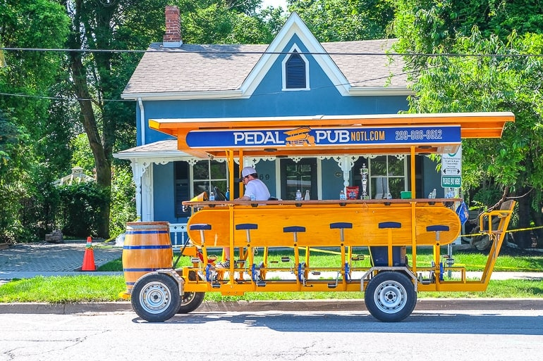 orange pedal pub bike parked on street in niagara on the lake
