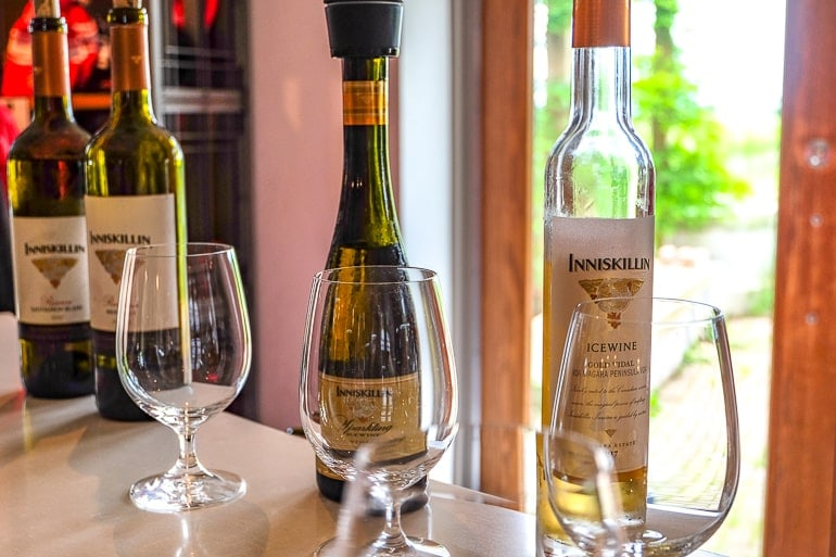 wine glasses on counter with bottles behind things to do in niagara on the lake wine tour