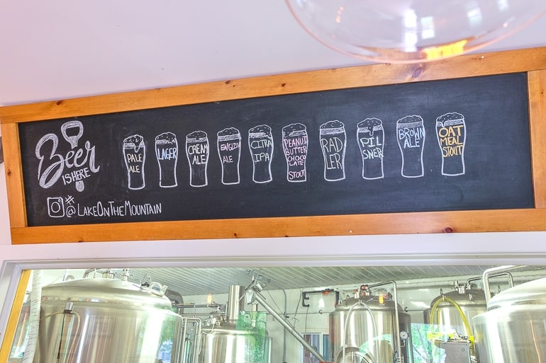 beer menu on chalkboard with metallic beer vats behind