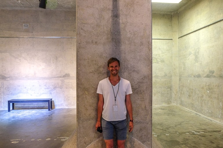 man standing up against concrete pillar in vaulted room