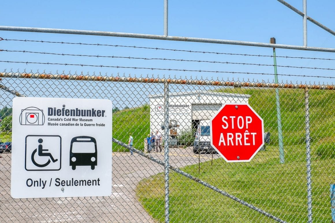 stop sign on chain fence with building behind diefenbunker museum carp