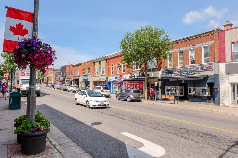 red brick shops with car in street in downtown huntsville ontario