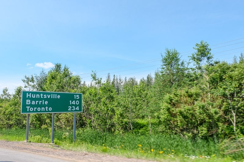 green highway distance sign on side of road in ontario